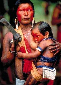 kayapo mother breastfeeding holding machetejpg