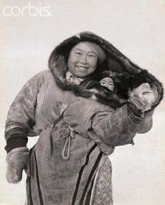 Smiling Inuit Mother Carrying Baby in Parka Hood